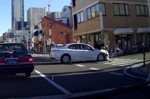 白いクルマが自転車を轢く